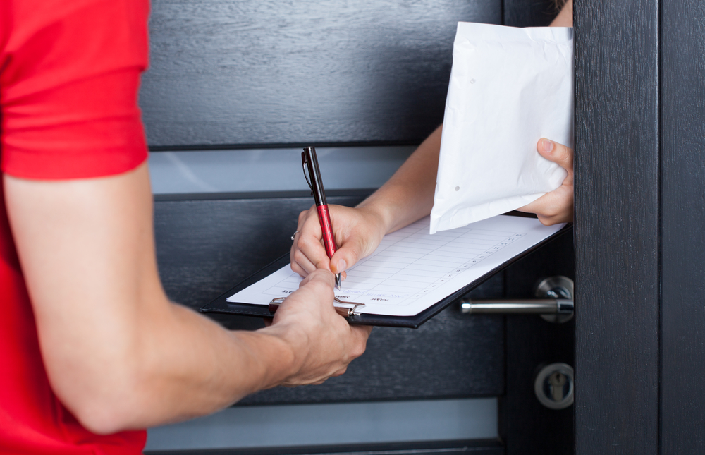Woman signing package delivery papers